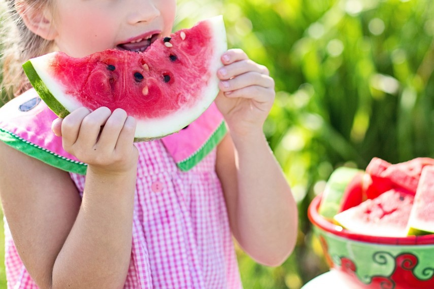 Young girl eating watermelon outside on sunny day