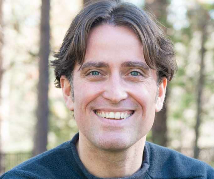 headshot of Dr. Philip Loring in front of a forest background