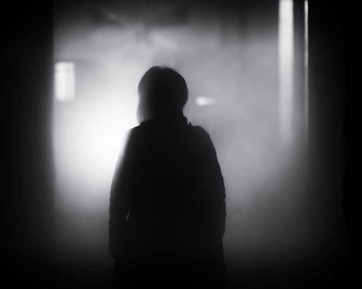 woman basked in shadow, standing in a dark alley.