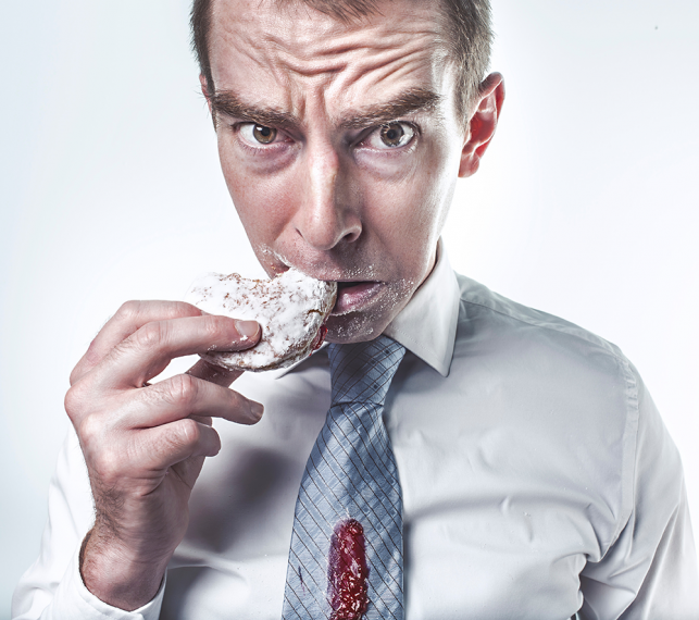 upset man eating a jelly donut with jelly on his tie