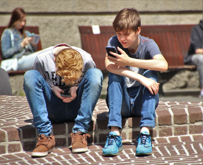 two boys sitting on the curb engrossed in their cell phones on a nice sunny day