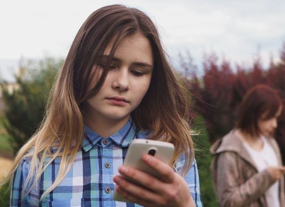 sad young girl checking messages on her phone. Other young girl in the background.