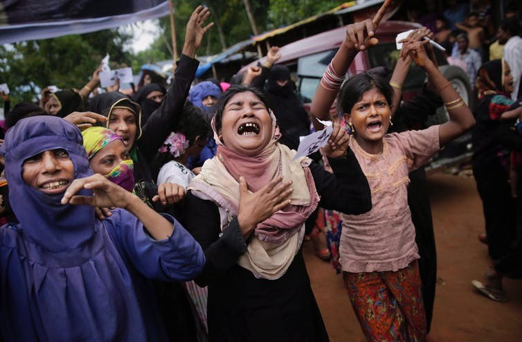 Rohingya women cry during a protest rally, August 2018