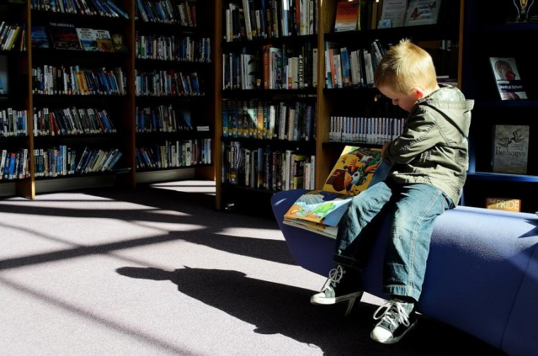 Image of child sitting in library reading a book