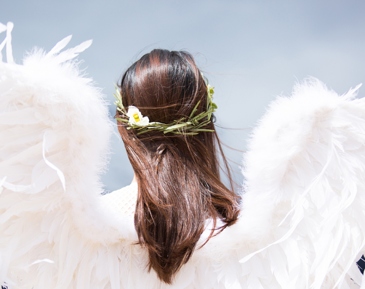 Picture taken from behind of torso and head of woman wearing angel wings.