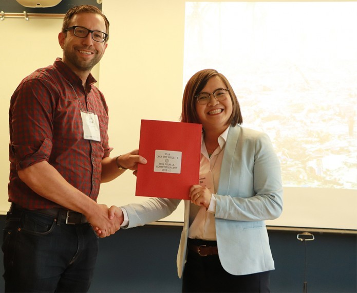 Yvonne Su shaking hands and receiving award for 3 minute thesis competition